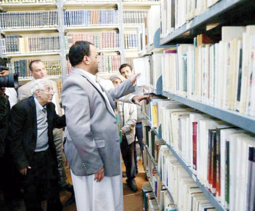 صورة أثارت غضب المثقفين ويبدو فيها المقالح خلف القيادي الحوثي صالح الصماد وهو ينتزع أحد الكتب من مكتبته الخاصة.