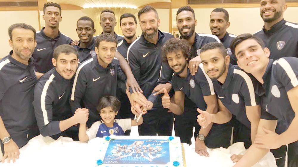 لاعبو الزعيم قبل تقطيع الكيكة المقدمة من نادي الكويت الكويتي احتفالاً ببطولة الدوري.