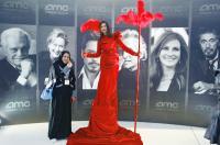 سيدة تتهيأ للقطة تجمعها بصور فنانين عالميين، ينتظر عرض أفلامهم قريباً. أثناء افتتاح أول دار عرض للسينما بمركز الملك عبدالله المالي، بالرياض، أمس الأول. (رويترز).