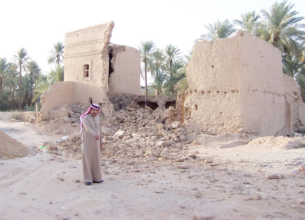الزميل الفهيد واقفاً على موقع منزل محمد بن عبدالوهاب بعد هدمه.. وتبدو أنقاض منزل مجاور.  (عكاظ)