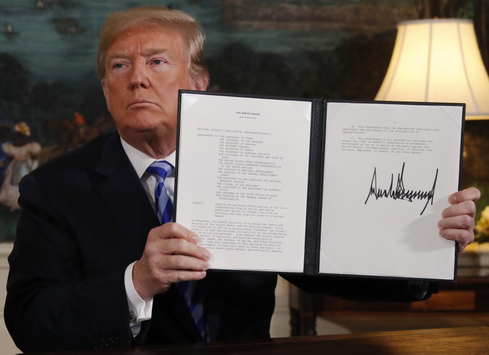 الرئيس الأمريكي دونالد ترمب يعرض مذكرة رئاسية بعد إعلان الانسحاب من الاتفاق النووي الإيراني في البيت الأبيض أمس. (رويترز)