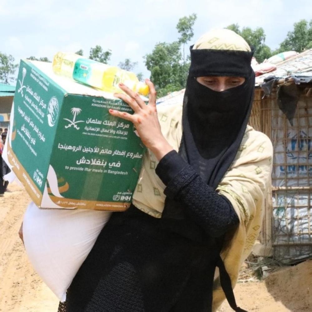 لاجئة روهينغية تحمل نصيبها من المساعدات. (واس)