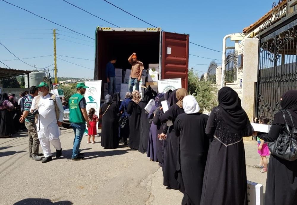 نازحات سوريات يتسلمن مساعدات سعودية. (عكاظ)