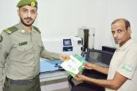 مواطن يستلم جواز سفره .(عكاظ)