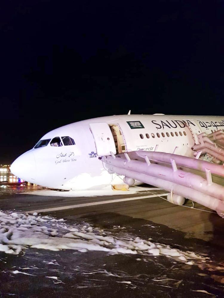 الطائرة وتظهر المزالق التي تم فتحها لإنزال الركاب. (عكاظ)