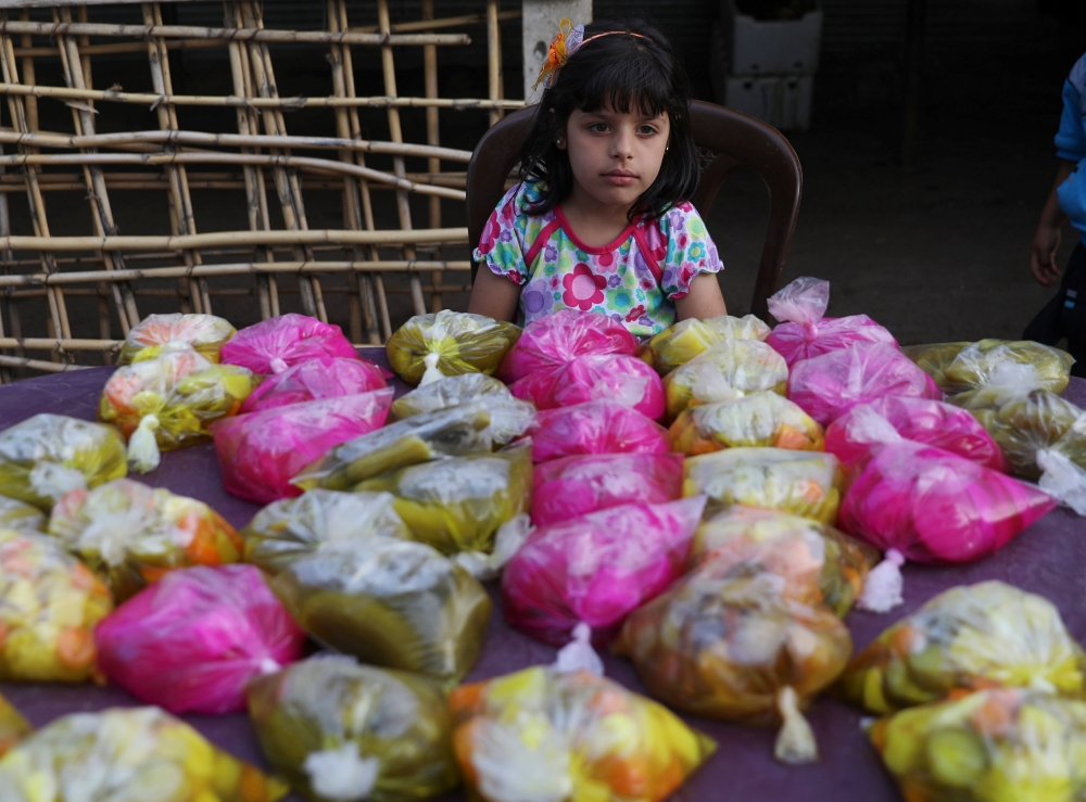 A girl sales pickled cucumber and pickles during the holy month of Ramadan in Zaizon camp in Daraa, Syria May 23, 2018.REUTERS/Alaa al-Faqir
