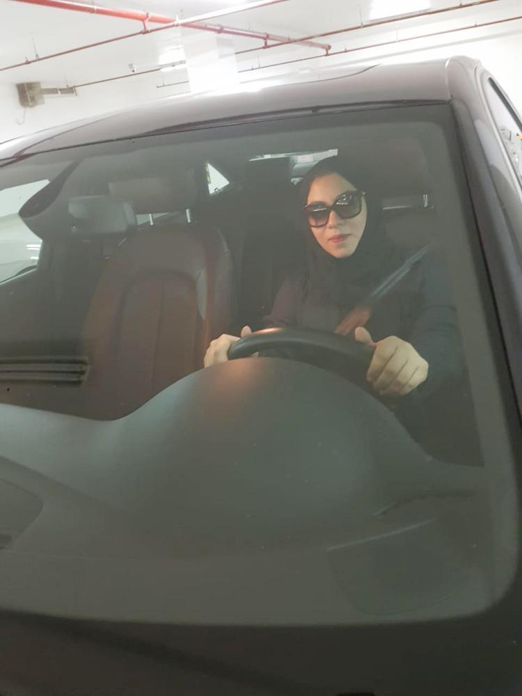 سيدة تتدرب على قيادة مركبة. (عكاظ)