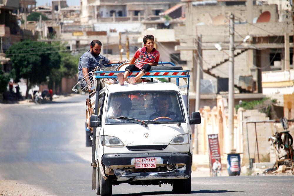 سوريون نازحون من درعا في طريقهم خارج المدينة فراراً من قصف النظام أمس. (أ. ف. ب)