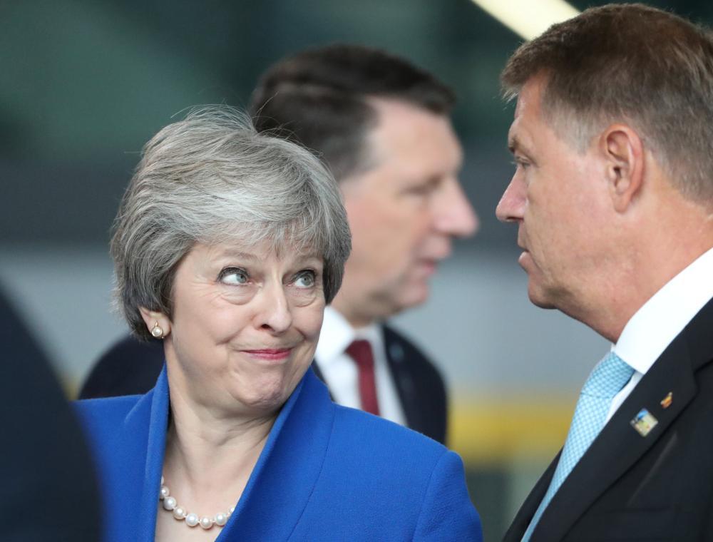 الرئيس الروماني كلاوس يوهانس في نقاش جانبي مع تيريزا ماي بمقر حلف الناتو. (رويترز)