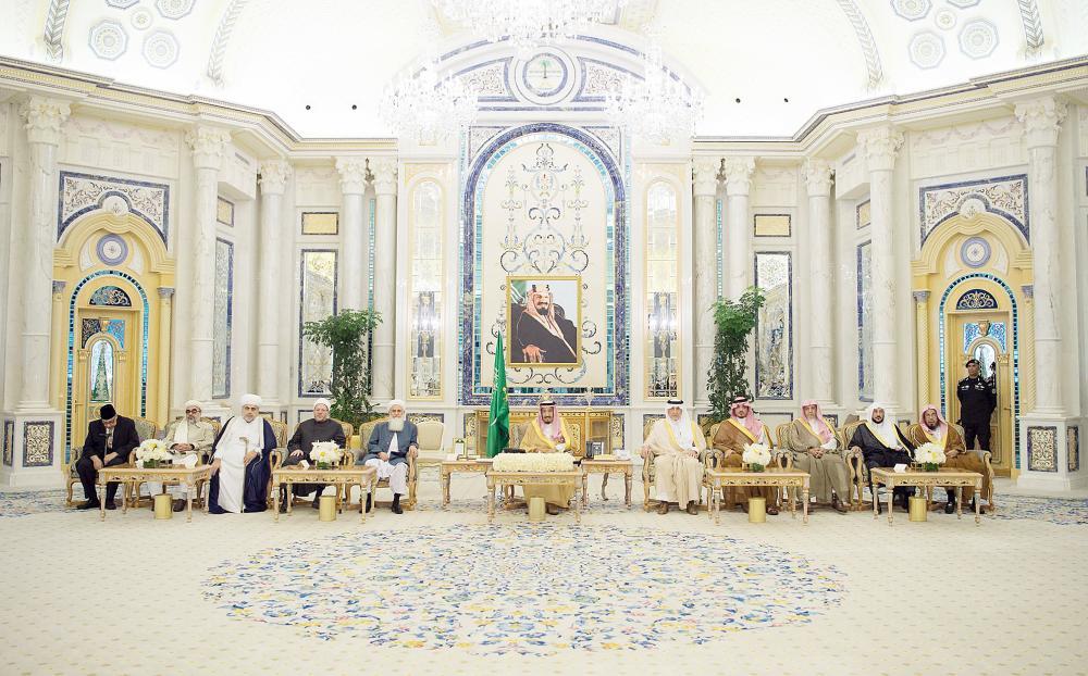 الملك سلمان مستقبلا المشاركين في المؤتمر الدولي لعلماء المسلمين حول السلم والاستقرار في أفغانستان أمس في جدة. (واس)