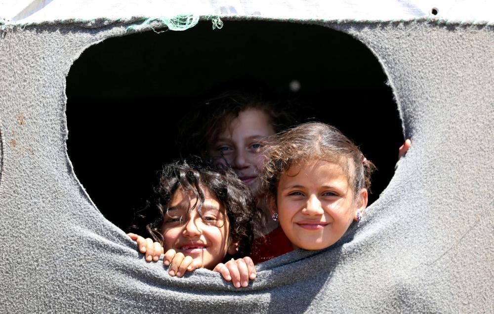 فتيات نازحات من درعا في أحد المخميات بالقرب من مرتفعات الجولان المحتلة، أمس الأول. (رويترز)