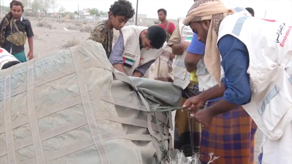 موظفو إغاثة ومواطنون يمنيون يتسلمون شحنة مساعدات. (وام)