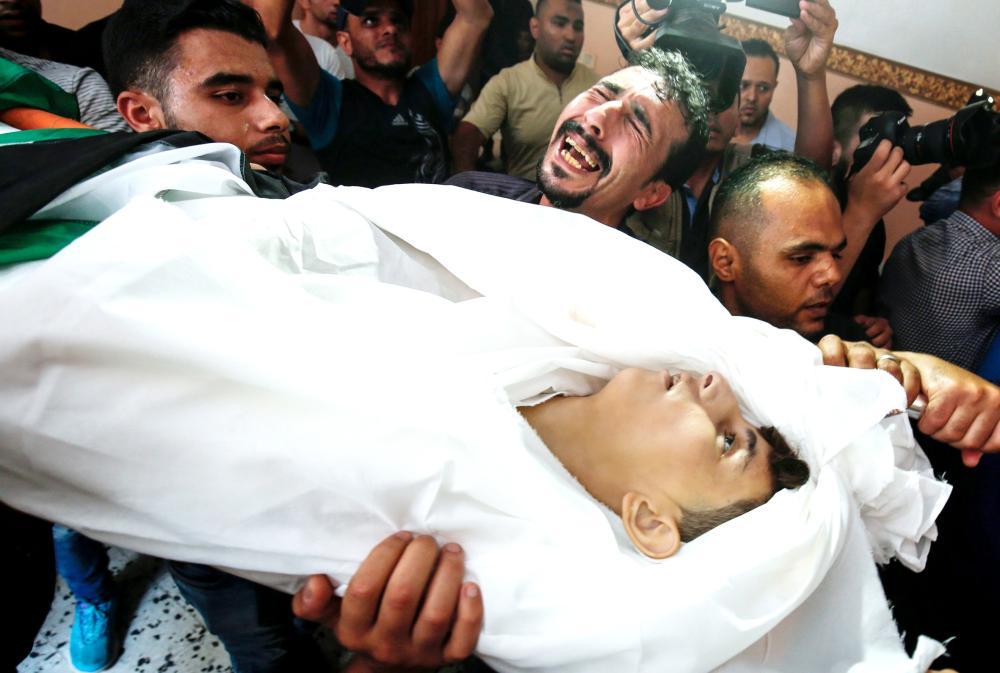 فلسطيني يبكي بحرقة أثناء تشييع صبي قتل في غارة إسرائيلية على غزة أمس.   (أ ف ب)