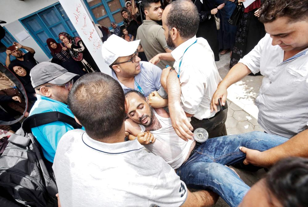 Palestinians help an employee of the United Nations agency for Palestinian refugees UNRWA  who reportedly tried to set himself on fire as fellow employees take part in a protest against job cuts announced by the agency, at its headquarters in Gaza City July 25, 2018. UNRWA announced today that it was cutting more than 250 jobs in the Palestinian territories after the United States held back hundreds of millions in aid.  / AFP / SAID KHATIB