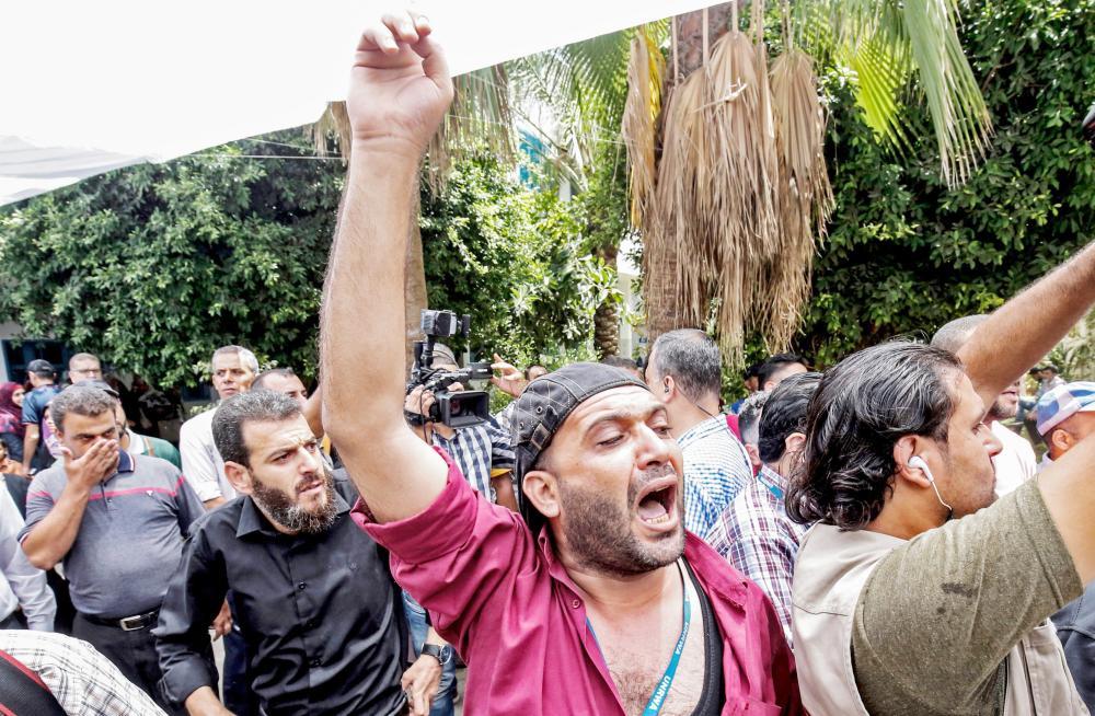 موظفون فلسطينيون يحتجون على فصلهم داخل مقر «الأونروا» في غزة أمس.  (أ.ف.ب)