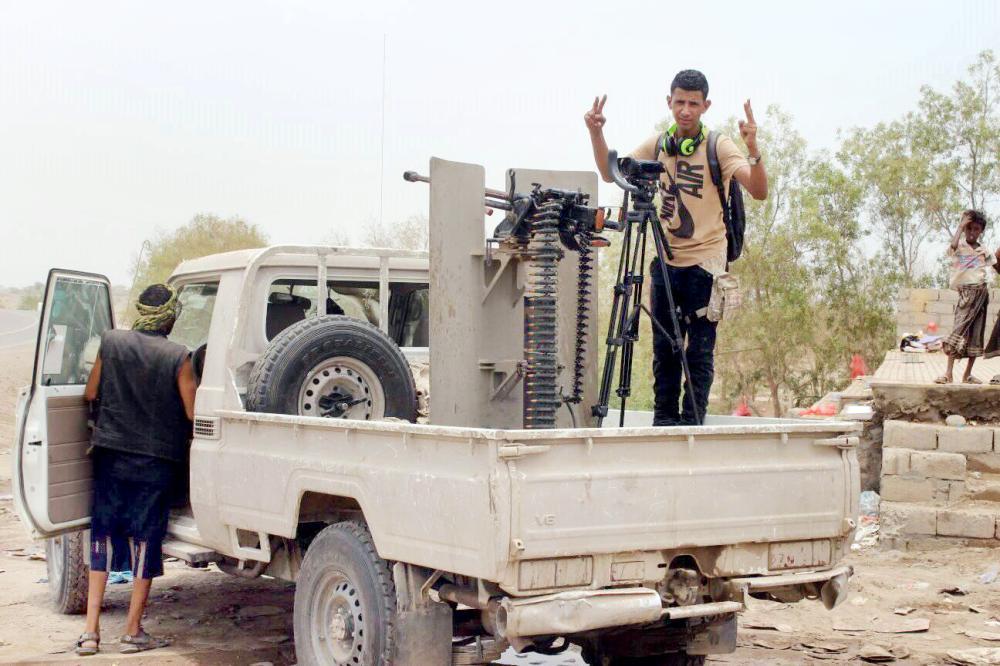 إعلامي يمني يؤشر بعلامة النصر على متن آلية عسكرية للجيش الوطني في الحديدة أمس. (عكاظ)