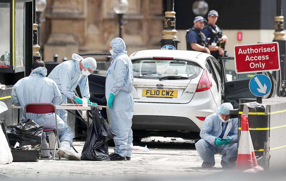 ضباط الأدلة الجنائية يرفعون البصمات من موقع حادثة الاصطدام أمام مبنى البرلمان البريطاني أمس. (أ ف ب)