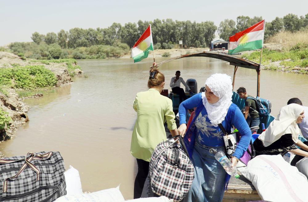أكراد من كردستان العراق يعبرون نهر دجلة لزيارة عائلاتهم على الجانب السوري قبيل عطلة العيد أمس الأول. (رويترز)