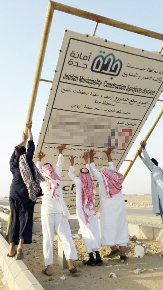 سكان الحي يرفعون لافتة المشروع بعد سقوطها. (تصوير: المحرر )