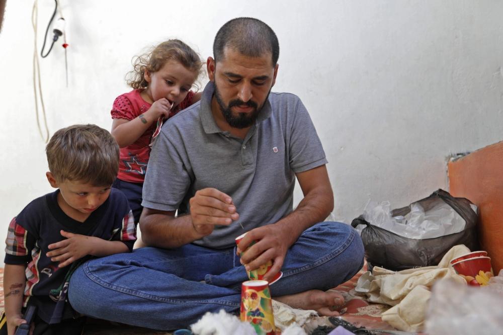 في إدلب.. أكواب كرتون محشوة بالقطن تتحول كمامات واقية من الغازات السامة