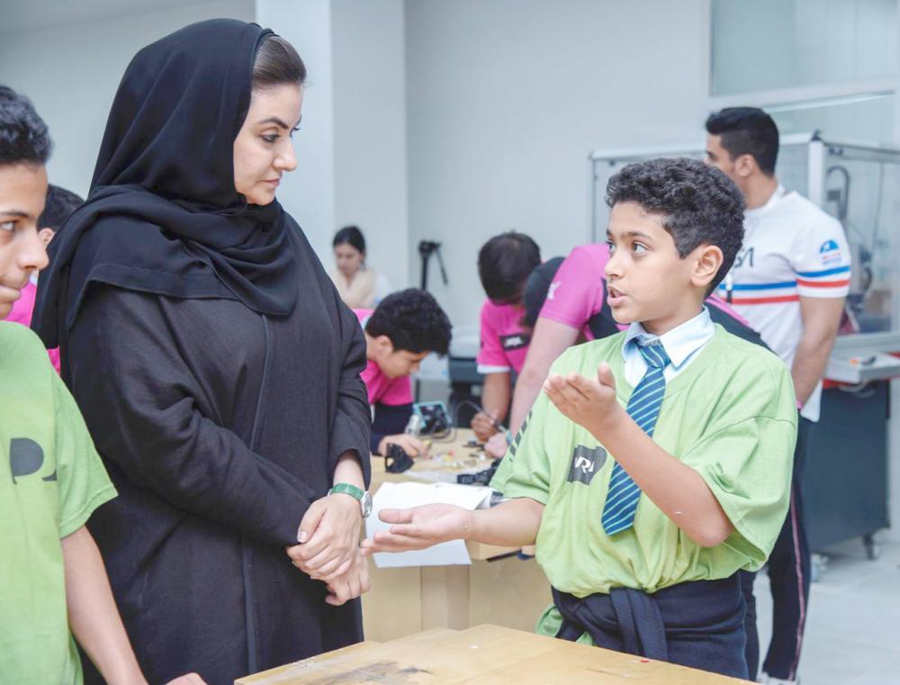 نوف الراكان تستمع لشرح أحد المشاركين في ورشة التعلم.