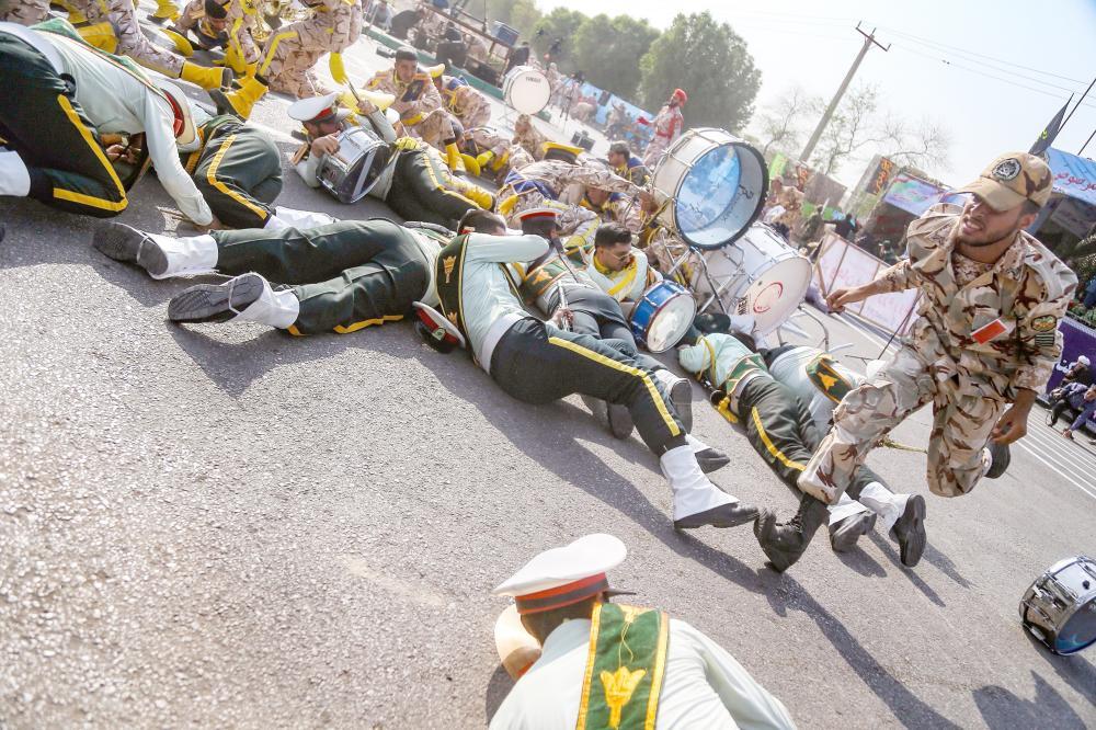 أعضاء من الفرقة العسكرية الموسيقية أثناء سقوطهم على الأرض خلال الهجوم على العرض العسكري في الأحواز.(أ. ف. ب)