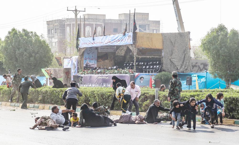 نساء وأطفال إيرانيون، مستلقين على الأرض بعد إطلاق النار على العرض العسكري.  (أ. ف. ب)