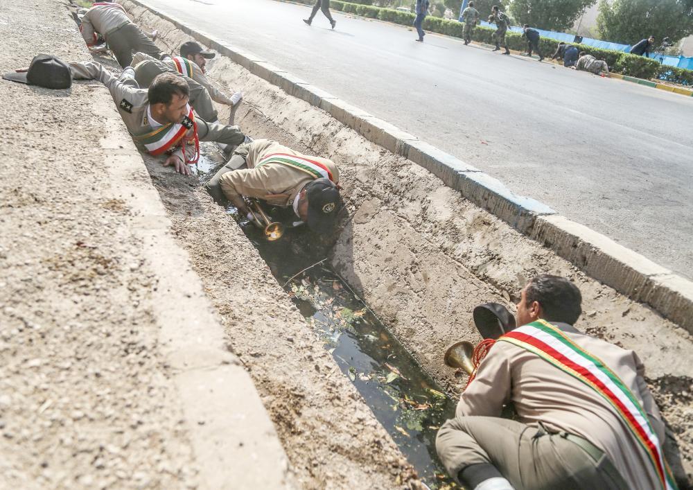 جنود الثوري الإيراني يتحصنون في مزراب للأمطار قبالة أحد الشوارع في مسرح الهجوم على العرض العسكري في الأحواز، أمس. (أ. ف. ب)