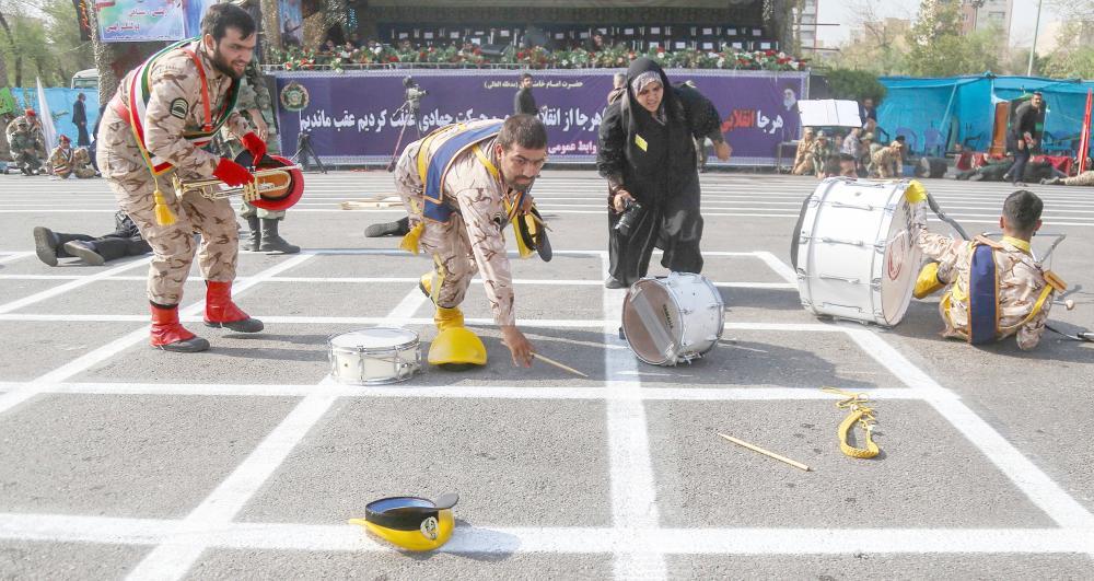 صورة لأعضاء فرقة عسكرية موسيقية تابعة للثوري الإيراني أثناء سقوطهم على الأرض خلال الهجوم على العرض العسكري في الأحواز. (أ. ف. ب)