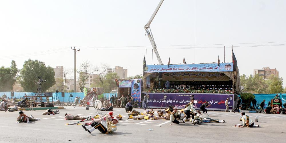 مصابون ممددين على الأرض في مسرح الهجوم على العرض العسكري. (أ. ف. ب)