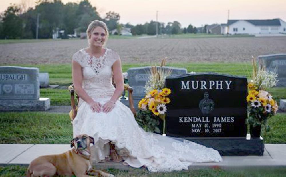 العروس بلباسها الأبيض بجوار قبر العريس.