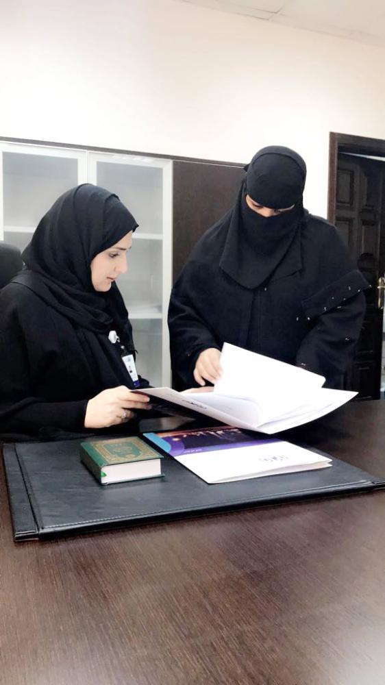 رئيسة البلدية النسائية تراجع معاملة مراجعة. (عكاظ)