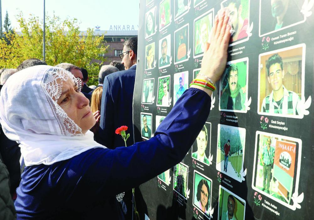 امرأة متأثرة أمام صور بعض الضحايا في العاصمة التركية أمس.