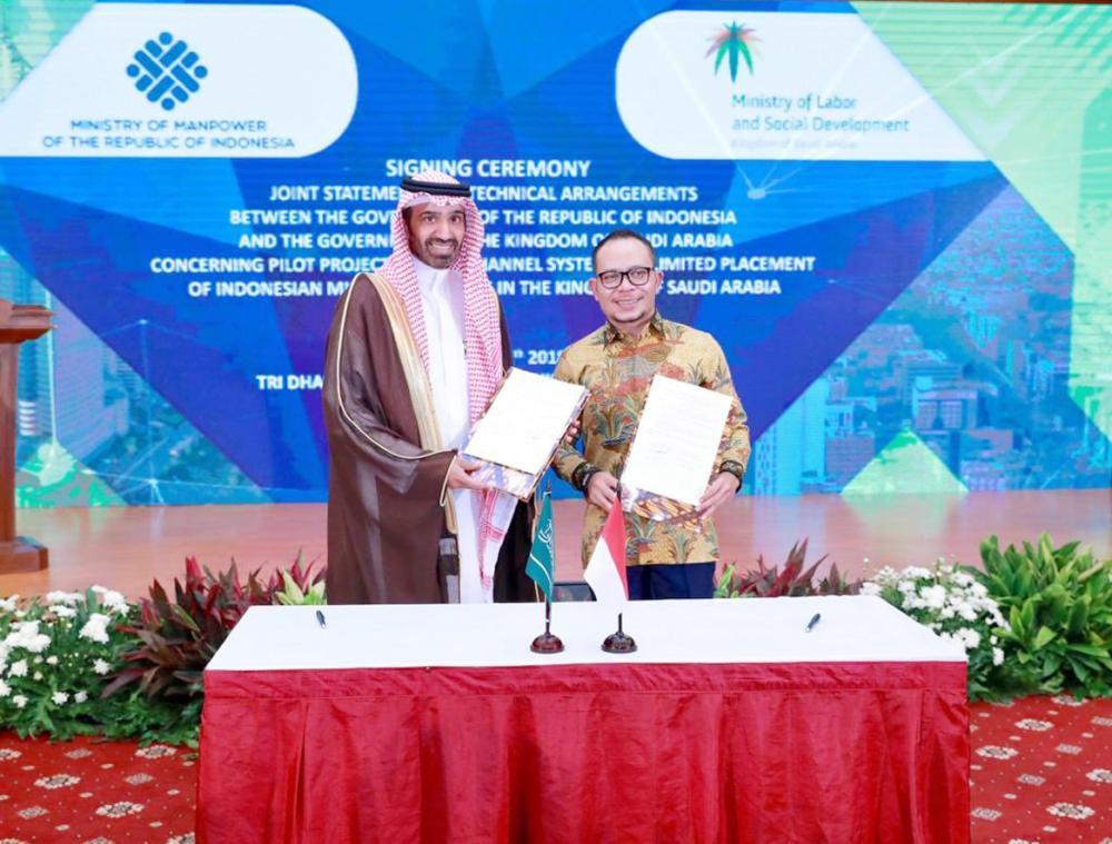 الراجحي أثناء توقيع عقد إعادة استقدام «الإندونيسية» مع وزير القوى العاملة.  (عكاظ)