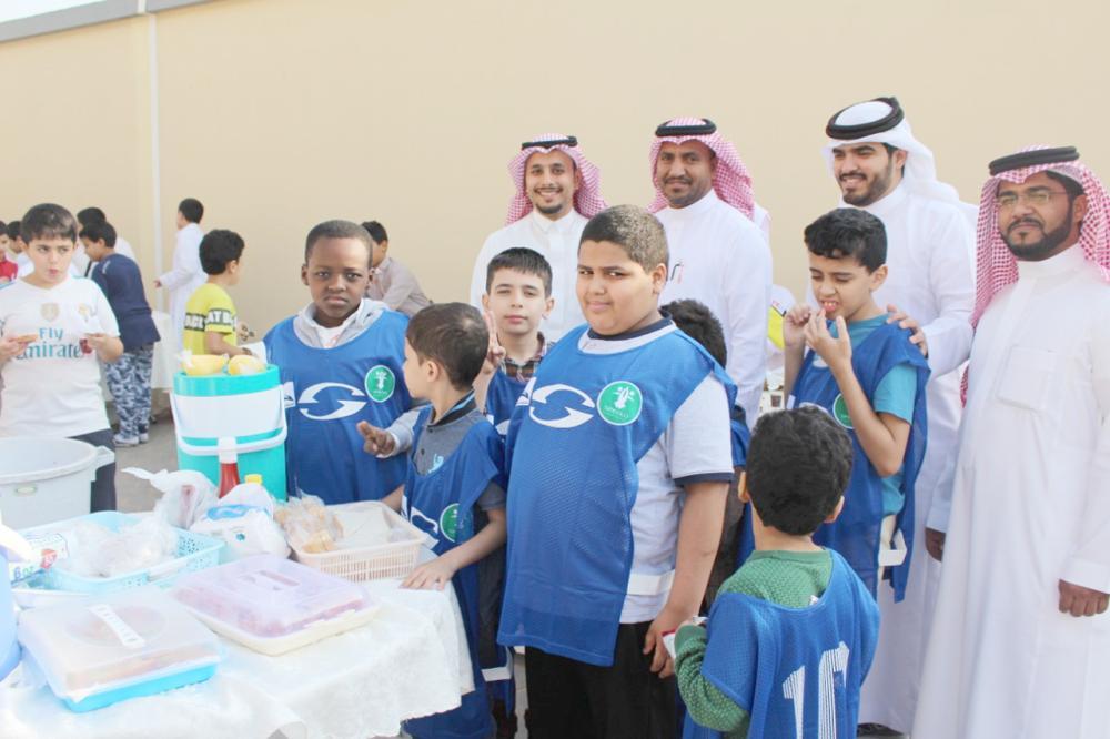 قائد المدرسة والمشرفون يتوسطون الطلاب المشاركين في البرنامج. (عكاظ)