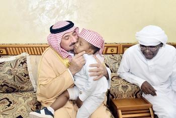 الأمير جلوي بن عبدالعزيز يقبل أحد أبناء الشهيد.