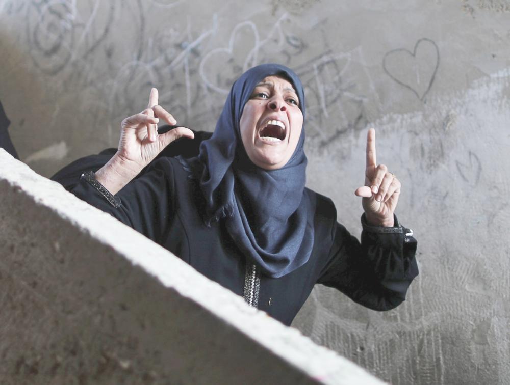 قريبة الفلسطيني خالد قويدر الذي قتلته إسرائيل تصرخ خلال جنازته في خان يونس جنوبي غزة أمس.  (رويترز)