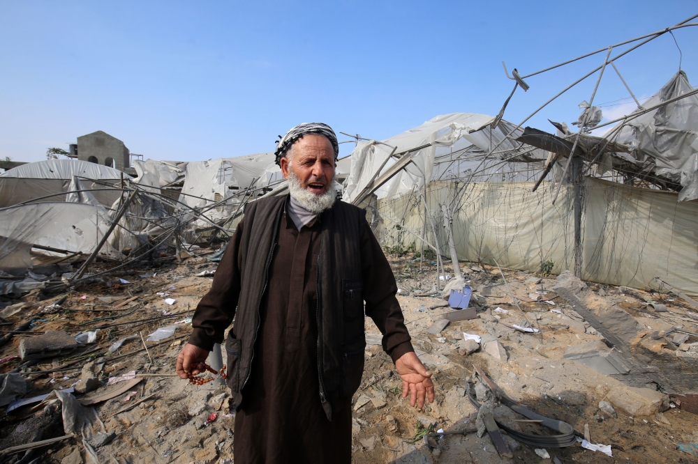 A Palestinian man gestures in front of a building damaged by an Israeli air strike earlier this week in Rafah in the southern Gaza Strip on November 14, 2018. A ceasefire held today after the worst escalation between Israel and Gaza militants since a 2014 war, but the situation remained volatile and the deal provoked sharp disagreement within the Israeli government. / AFP / SAID KHATIB