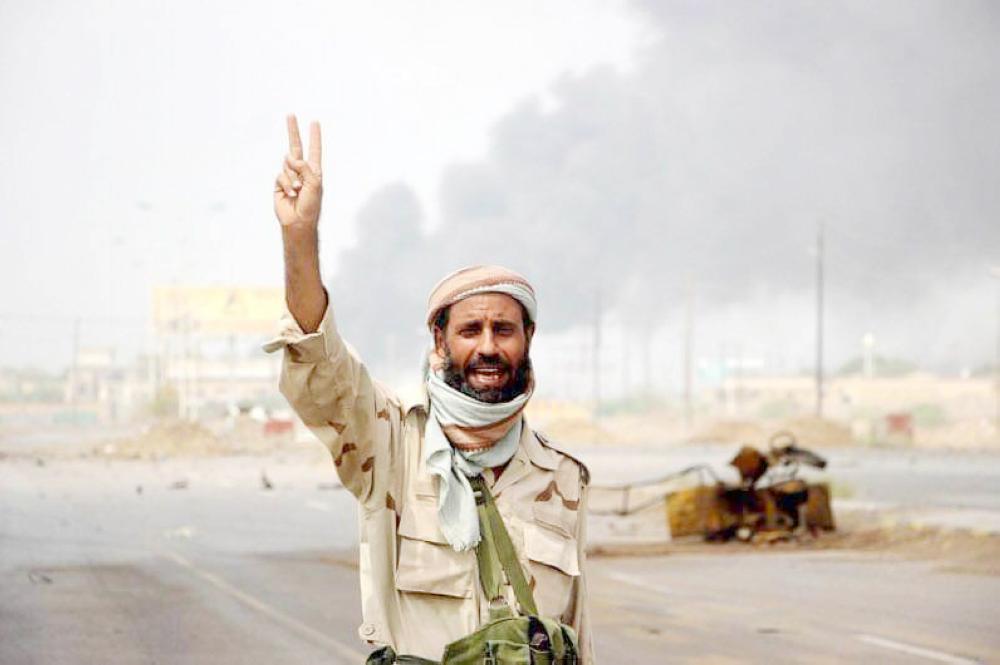 جندي يمني يلوح بعلامة النصر في شارع صنعاء شرقي الحديدة أمس. (متداولة)