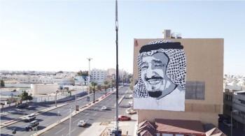 جدارية بمناسبة زيارة الملك سلمان إلى تبوك على أحد المباني في المدينة.