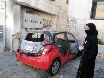 نورهان تقف إلى جوار سيارتها المحترقة. (عكاظ)