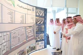 الأمير عبدالله بن بندر مطلعا على خريطة مشروع مدينة السيارات.