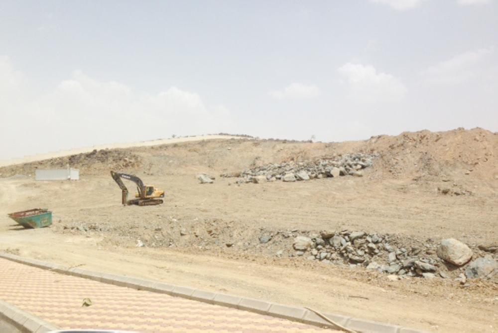 معدات ثقيلة تعمل على تسوية مواقف الطالبات لمجمع البنات بغثران. (عكاظ)