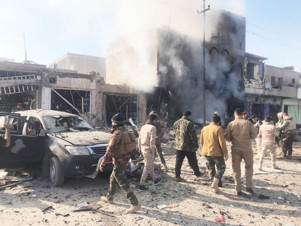 دخان يتصاعد بعد انفجار سيارة مفخخة في بلدة القائم الحدودية العراقية أمس. (رويترز)