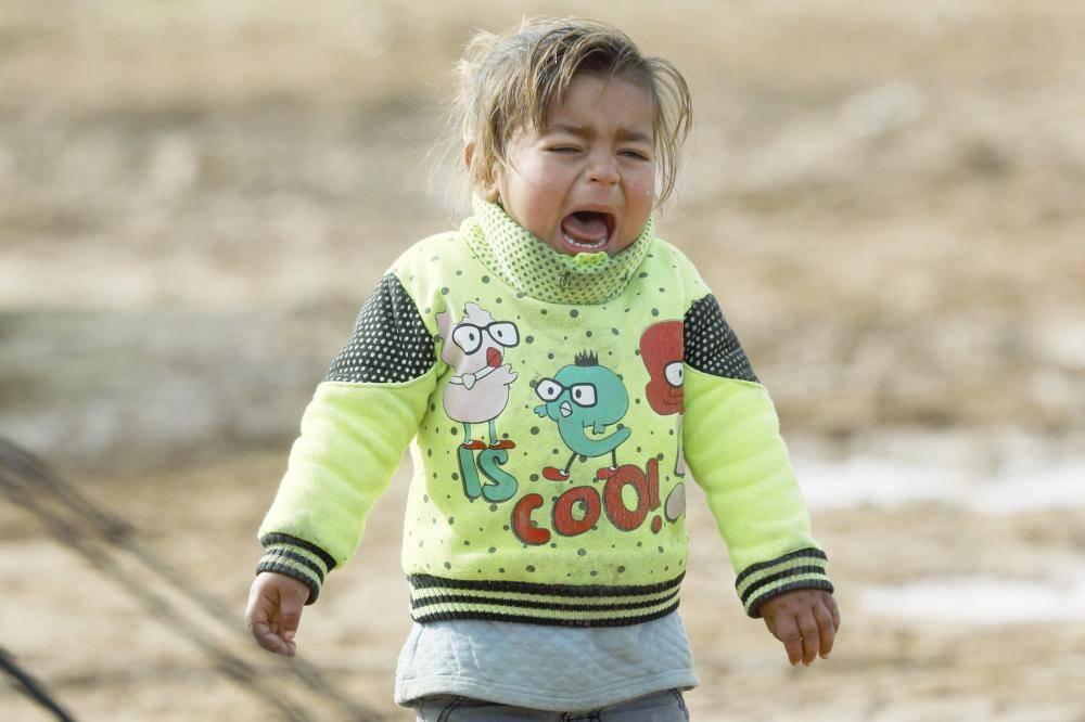 طفلة سورية تبكي من شدة البرد في مخيم للنازحين بدير الزور أمس الأول. (أ ف ب)