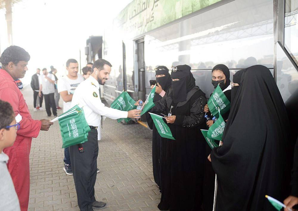 موظفو الجمارك يقدمون الأعلام للجماهير السعودية.