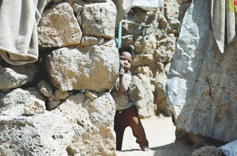 طفلة يمنية تقف خارج كوخ أسرتها في مخيم مؤقت للنازحين قرب صنعاء أمس. (رويترز)