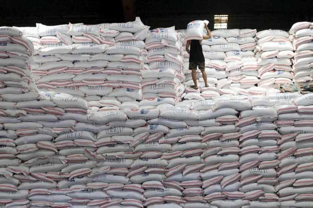 A worker carries a sack of rice inside a National Food Authority (NFA) warehouse in Taguig city, south of Manila, August 25, 2015. The Philippines aims to increase rice production by as much as 6.5 percent next year after an expected fall in this year's output, with state spending to boost crop yields helping to offset possible losses from the El Nino dry weather condition, a senior official said on Tuesday. REUTERS/Romeo Ranoco