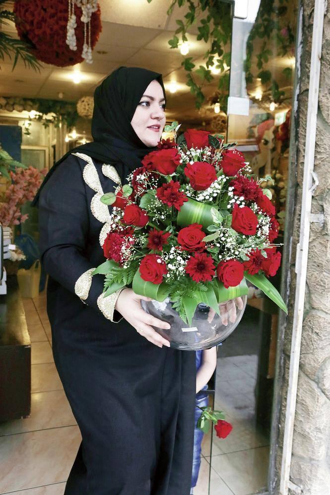 سيدة تحمل باقة ورد في أحد محلات الورود في محافظة جدة، التي شهدت إقبالا كبيرا أمس بمناسبة الاحتفال بيوم الفالنتاين. (تصوير: مديني عسيري)
