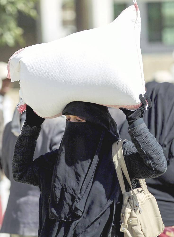 يمنية تحمل كيس حبوب تلقته من جمعية خيرية محلية للمتضررين في صنعاء أمس الأول. (أ ف ب)